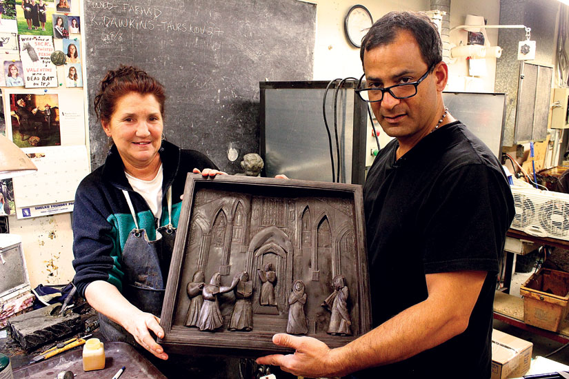 Sculptor Farhad Nargol O'Neil and Holly Atkinson display one of 20 panels for the new bronze doors. (Photo courtesy of Concrete Pictures Inc.)