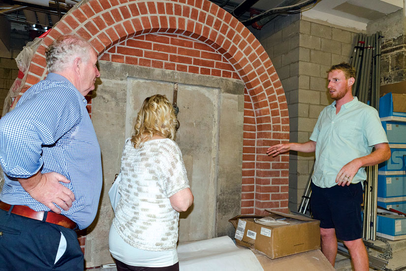Tomas Nugent shows off his handiwork in the crypts to his parents, Michael and Kathleen. Nugent is carrying on the work of the Irish immigrants who built St. Michael's in the 1840s. (Photo by Evan Boudreau)