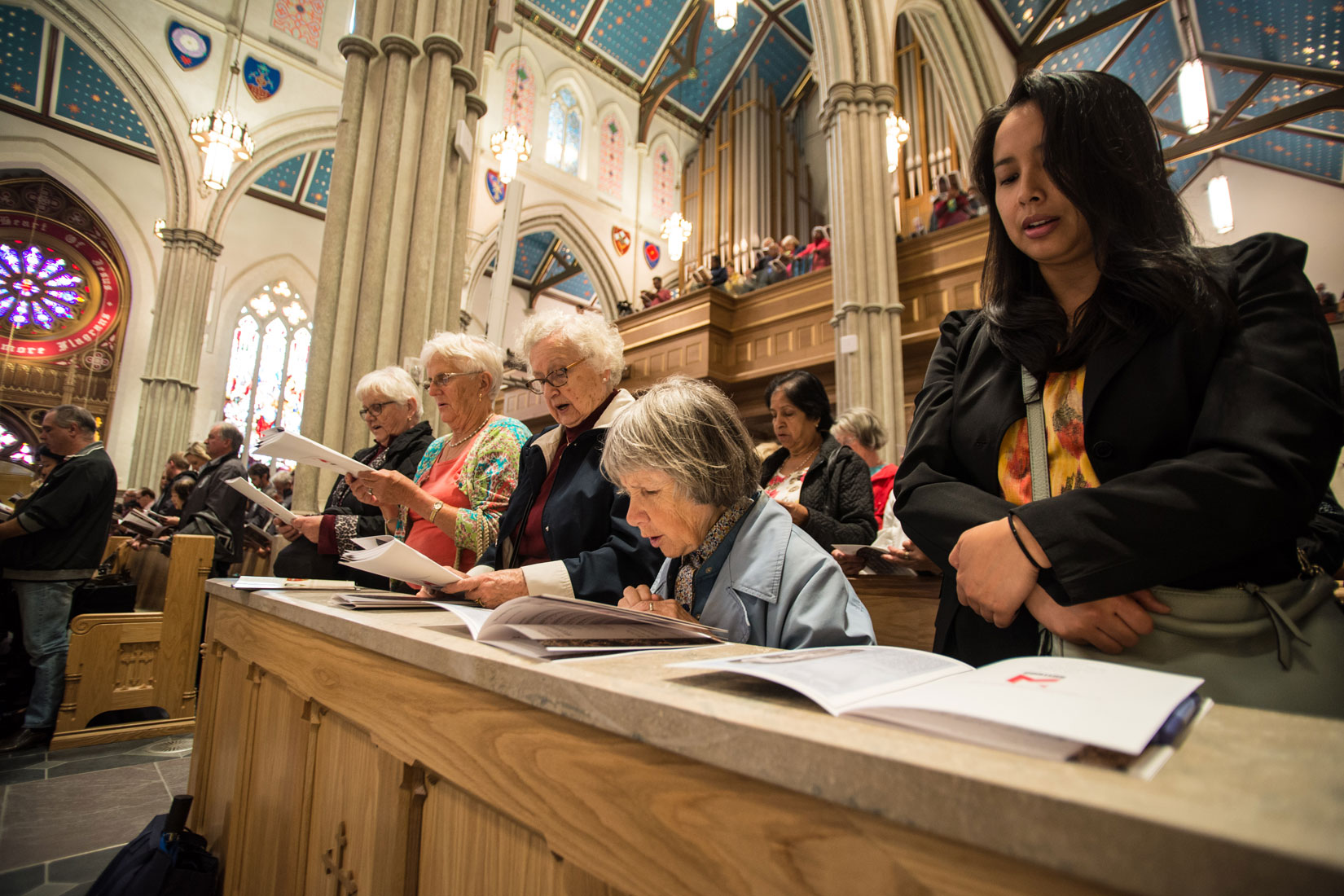 Women praying at the workers' thanksgiving Mass at St. Michael's Cathedral Sept. 30. (Photo by Michael Swan)