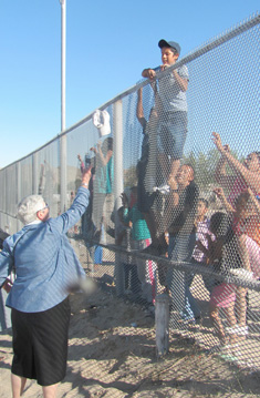 Sister Marie tosses hats over the fence that separates New Mexico and Mexico Oct. 14.