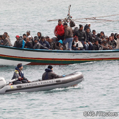 Migrants from North Africa arrive by boat, escorted by two members of an Italian security force, at the southern Italian island of Lampedusa March 14. More than 22,000 refugees, many fleeing political unrest in Tunisia and Libya, have arrived on the tiny island since January. (CNS photo/Stefano Rellandini, Reuters)