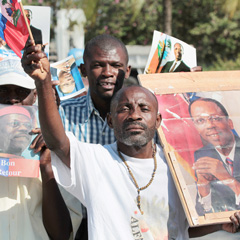 Supporters of former Haitian President Jean-Bertrand Aristide cheer before his arrival outside the international airport in Port-au-Prince. (CNS photo)