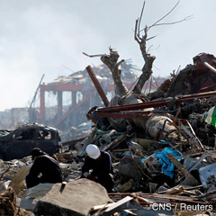 Men sit amid debris in an area that was destroyed by the March 11 earthquake and tsunami, in Minamisanriku, Miyagi prefecture, in northern Japan, April 6. (CNS photo/Toru Hanai, Reuters)