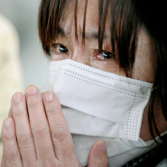 A woman weeps after being told of the death of relatives. Japanese officials are estimating that 10,000 people may have lost their lives. (CNS photo/Reuters/Kyodo)