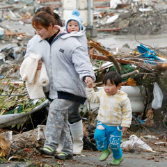 A woman and children walk past rubble in Minamisanriku, northeastern Japan March 16. More than 400,000 people were made homeless. (CNS photo/Kyodo/Reuters)