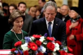 Former U.S. President George W. Bush and former first lady Laura Bush stand at the flag-draped casket of former U.S. President George H.W. Bush as he lies in state inside the U.S. Capitol rotunda Dec. 4 in Washington. George H.W. Bush, the 41st president of the United States, died in his Houston home Nov. 30 at age 94.
