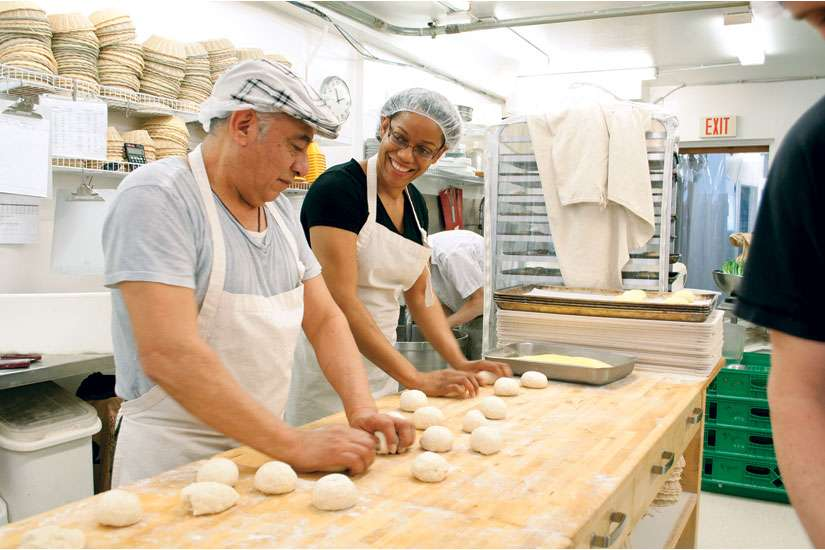 Chimal and Wendy exchange jokes as they knead a batch of English muffins at Toronto's St. John's Bakery.