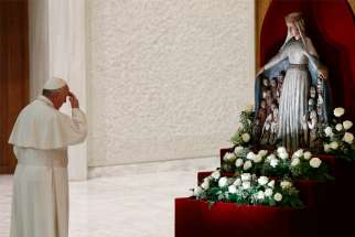 Pope Francis makes the sign of the cross as he prays in front of a statue of Mary in 2016 at the Vatican.