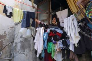 A woman removes dry clothes from her home in a poor section of Tripoli, Lebanon, July 1, 2020. Lebanese have seen their national currency lose 80% of its value against the U.S. dollar, a majority currency also used in the country, since nationwide protests erupted in October.