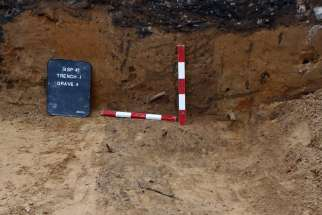 A gravestone is uncovered under the parking lot at St. John the Evangelist Church in Toronto