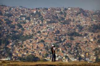 A man and his daughter overlook a neighbourhood in Caracas, Venezuela, March 25. Venezuela's opposition party hopes Pope Francis will media discussions with the government to find a solution to the country's deepening economic crisis.