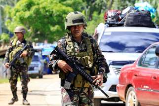 Philippine government troops stand guard May 24 at a checkpoint along a main highway in Lanao del Norte province. Residents started to evacuate the town of Marawi after President Rodrigo Duterte imposed martial law across the entire Muslim-majority region of Mindanao.