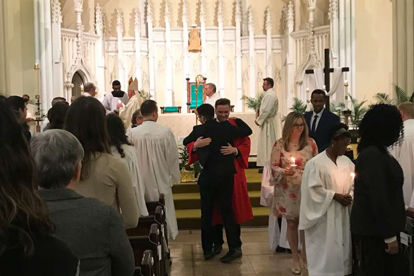 Stewart Langley hugs his sponsor, Jose Arnal, after he was confirmed this past Easter at St. Mary's Cathedral in Kingston.