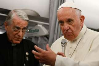 Pope Francis speaks to journalists aboard his flight from Sarajevo, Bosnia-Herzegovina, to Rome June 6. At left is Jesuit Father Federico Lombardi, the Vatican spokesman. The pope announced on the return flight that a decision soon will be announced conc erning alleged Marian apparitions in Medjugorje, Bosnia-Herzegovina.