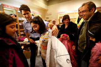 Prime Minister Justin Trudeau helps a young Syrian refugee try on a winter coat after she and her family arrived in Toronto from Beirut in December 2015.