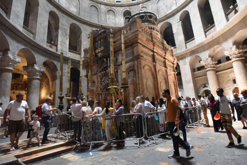 Tourists walk around the tomb in the Church of the Holy Sepulcher in Jerusalem's Old City, June 13, 2019. Following the successful cooperation on the 2016 restoration of the Edicule in the Church of the Holy Sepulcher, the leaders of the Greek Orthodox, Catholics and Armenian Orthodox, who serve as guardians of the holy site, have signed an agreement to continue with restorations, this time on the pavement and foundations around the tomb.