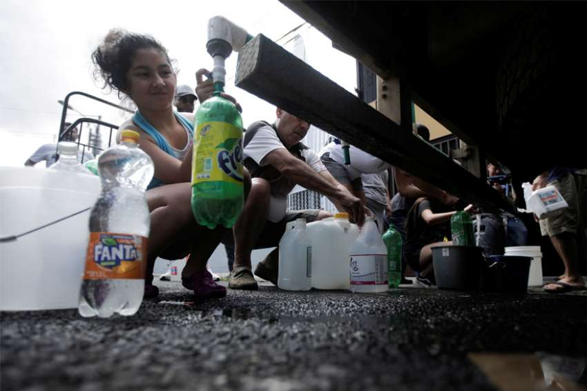 People collect clean drinking water from a tanker sent by government authorities as part of measures to help prevent the spread of the coronavirus in San Jose, Costa Rica, March 14, 2020. The Vatican said defending the right to clean water is part of the Catholic Church's promotion of the common good.