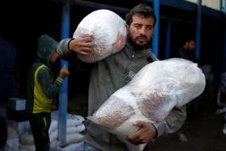A Palestinian carries food supplies at a United Nations food distribution center in the Al-Shati refugee camp in Gaza City Jan. 15.