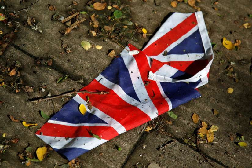 A British flag which was washed away by heavy rains lies on the street in London June 24, 2016 after Britain voted to leave the European Union in the Brexit referendum.