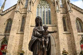 St. Michael's Cathedral in downtown Toronto is seen behind a statue of Mary with the Child Jesus.