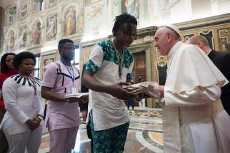 Pope Francis meets at the Vatican Feb. 12 with Italian young people, adults and migrants rescued from human traffickers. The pope responded to the questions five of the young people asked about preventing trafficking and assisting survivors.