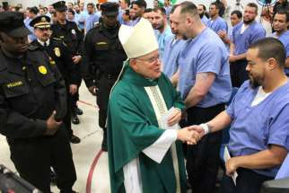 Archbishop Charles J. Chaput of Philadelphia greets inmates of Curran-Fromhold correctional facility in Philadelphia during a visit in mid-January. Pope Francis has a planned visit to the prison Sept. 27 during his two-day visit to the city.