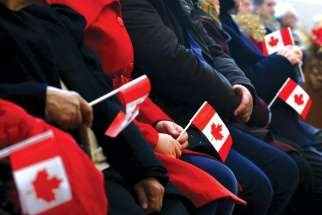 Syrian refugees hold Canadian flags in a welcome service in 2015 at a church in Toronto. Statistics show a dramatic shift in the number of government-assisted refugees versus private sponsorships.