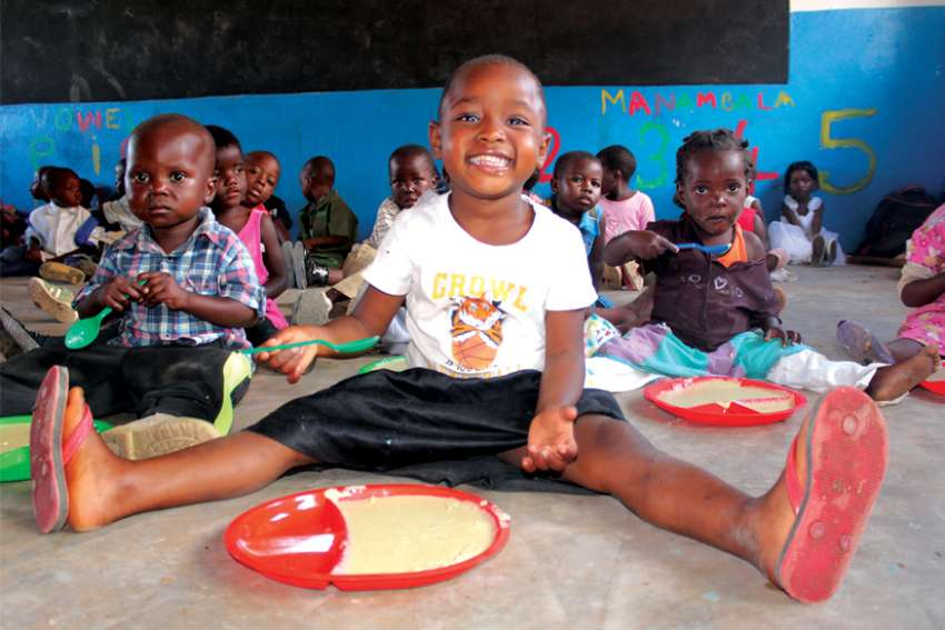 Children in a Malawi school sit down for a meal.