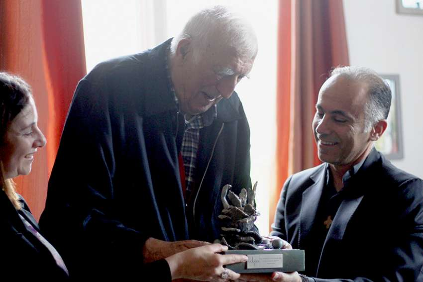 Father Fadi Daou, right, president of Adyan, and Nayla Tabbara, also of Adyan, present the Spiritual Solidarity Award to Jean Vanier, founder of the International Federation of L'Arche Communities, Oct. 6 in Trosly, France. Adyan is a foundation for interreligious studies and spiritual solidarity based in Lebanon.