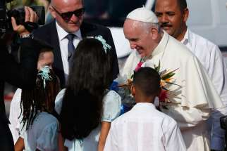 Pope Francis accepts flowers from children as he arrives at Antonio Maceo International Airport in Santiago, Cuba.
