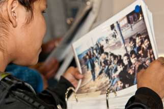 An Indigenous woman looks through archived photos of residential schools in Canada.