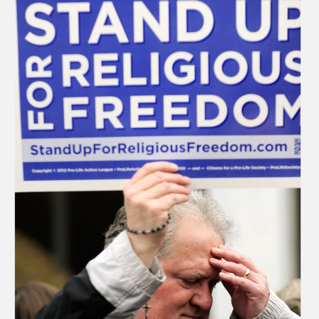 "Dan Cumberledge, a parishioner of Nativity of the Blessed Virgin Mary Church in Brockport, N.Y., holds a rosary and a sign as he takes part in a ""Stand Up for Religious Freedom"" rally. On May 14, the CCCB issues a Pastoral Letter on Freedom of Conscience and Religion."