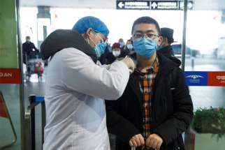 A medical official takes the body temperature of a man Jan. 27, 2020, at the departure hall of the airport in Changsha, China, as the country is hit by an outbreak of a new coronavirus. The virus has spread to almost every province in mainland China during Lunar New Year.