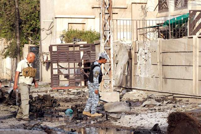 Security personnel inspect debris outside the Syrian Catholic cathedral in Baghdad, Iraq, in November, 2010 after dozens of hostages and police were killed when security forces raided the cathedral to free worshippers being held by gunmen wearing explosives.