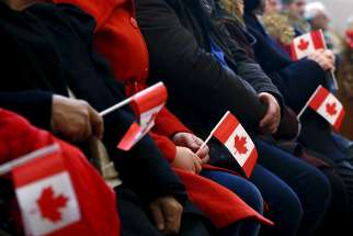 "Syrian refugees hold Canadian flags as they take part in a welcome service in 2015 at a church in Toronto. The Catholic Church and Catholic agencies that work with migrants and refugees around the world are called to educate, advocate and seek alternative host countries in the face of a growing ""refusal to welcome"" newcomers, said a top Vatican official."