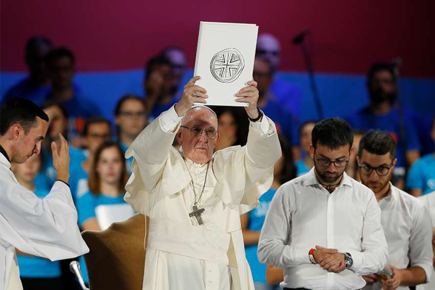 Pope Francis raises the Book of the Gospels during an evening meeting with Italian young adults at the Circus Maximus in Rome Aug. 11.