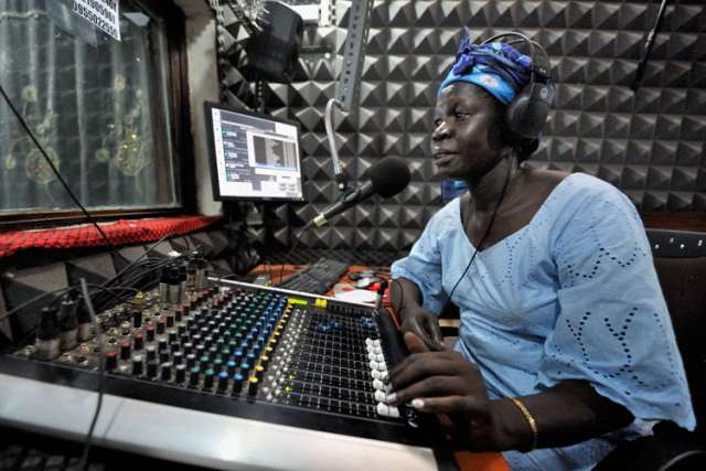 "Melania Itto, program manager of Radio Bakhita, hosts the morning ""Juba Sunrise"" program in the station's studio in Juba, Southern Sudan. Radio Bakhita has been silent since Aug. 16 when South Sudan's National Security Service stormed into the station and arrested its news editor."