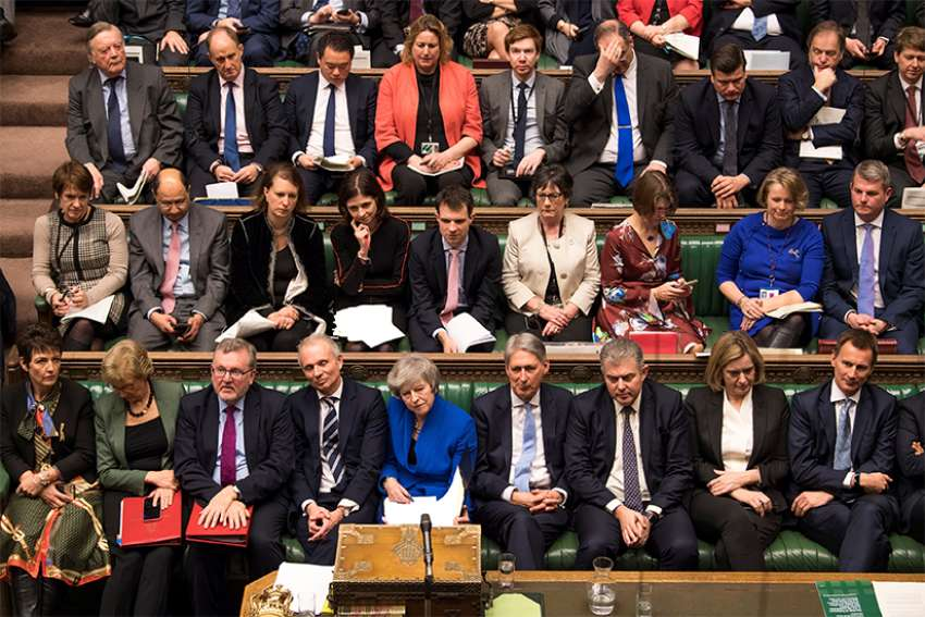British Prime Minister Theresa May, center in blue, reacts during a no-confidence debate Jan. 16, a day after Parliament rejected her Brexit deal in London.