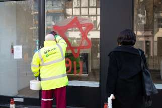 "A worker removes anti-Semitic graffiti on a shop window in the Belsize Park neighborhood of London. Cardinal Vincent Nichols of Westminster used his New Year message to condemn the graffiti, saying such hatred ""shames us all"" and can have no place in society."