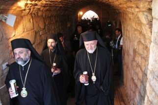 Members of the clergy hold candles during a vigil at the Balamand Monastery in Koura, Lebanon, June 22, to pray for the release of bishops kidnapped in northern Syria. Orthodox Metropolitan Paul of Aleppo and Syriac Orthodox Metropolitan Gregorios Yohanna of Aleppo were kidnapped April 22, 2013 in northern Syria while on a humanitarian mission.