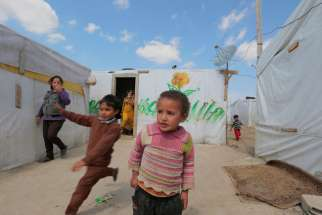 Syrian children play at a makeshift settlement in Bar Elias, Lebanon, March 15, 2015.