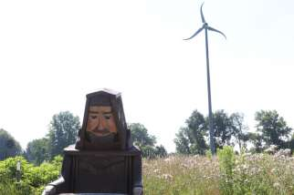"A wooden figure of St. Francis of Assisi is perched in the yard of the energy-efficient straw-bale house built by a Catholic religious order in Ohio. Pope Francis' second encyclical on the environment is called ""Laudato Si"" and is named after a St. Francis of Assisi prayer. Pope Francis calls everyone to be a steward of the Earth."
