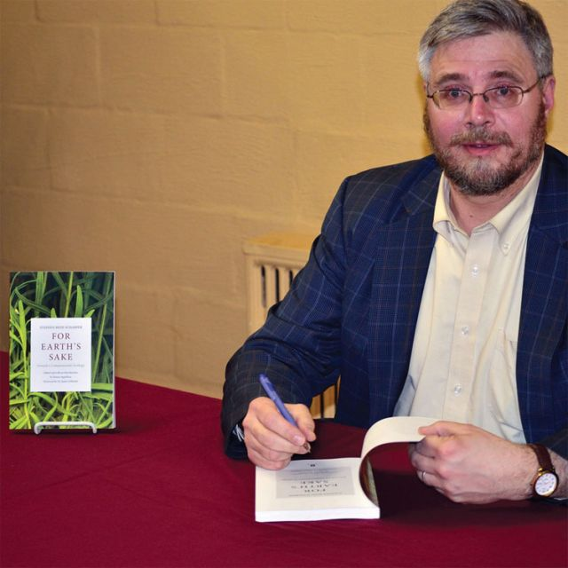 Stephen Scharper signs a copy of his latest book, For Earth's Sake, after giving an hour-long lecture on the role of religious imagination in dealing with the environmental crisis.