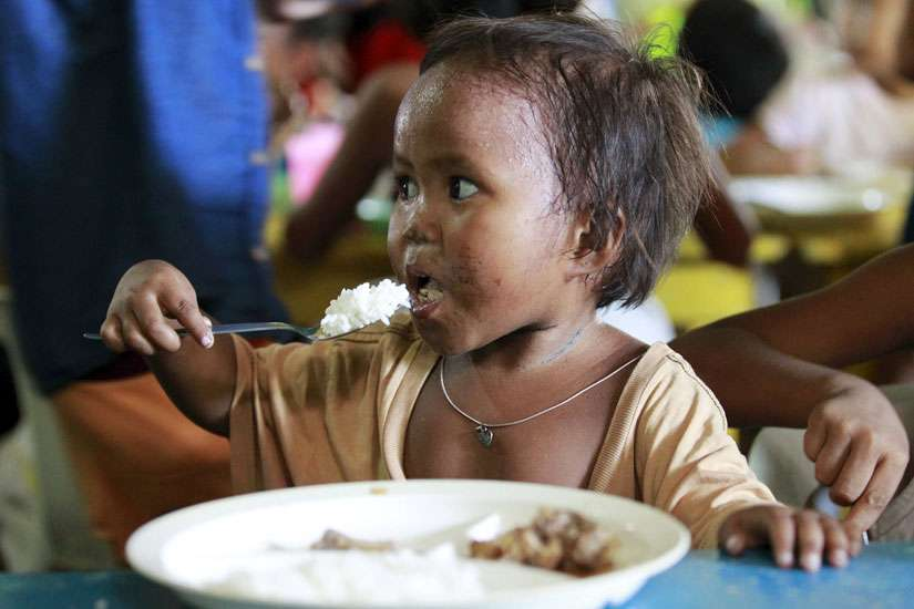 A boy eats a free meal during a July 20 feeding program at a slum area in Manila, Philippines. The head of the Philippine bishops' conference said helping the poor and getting rid of political dynasties should be front and center in the months leading up to the country's May elections.