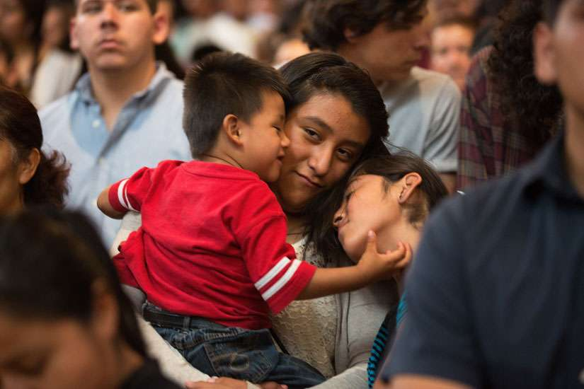 A woman holds onto her children during a special Mass in Los Angeles honouring immigrants.