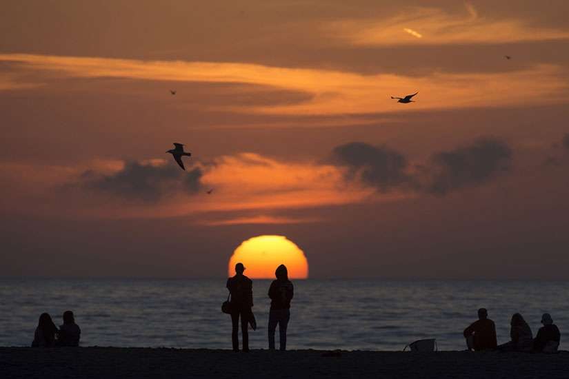 People sit on the beach and watch the sun set as seagulls fly over head in Santa Monica. On Thursday, California's physician-assisted dying law, passed in 2015, will come into effect.