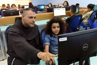Franciscan Father Mario Hadchity sits with Sara Wajne July 18 in the computer lab at the new youth center in Jericho, West Bank.