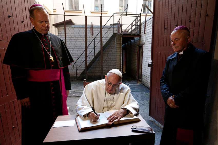 Pope Francis signs a guest book after visiting the Museum of Occupations and Freedom Fights in Vilnius, Lithuania, Sept. 23. At left is Archbishop Gintaras Grusas of Vilnius.