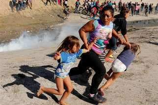 A Honduran migrant family who are part of a caravan trying to reach the U.S. run from tear gas released by U.S. border patrol near Nov. 25 the fence between Mexico and the United States in Tijuana, Mexico.