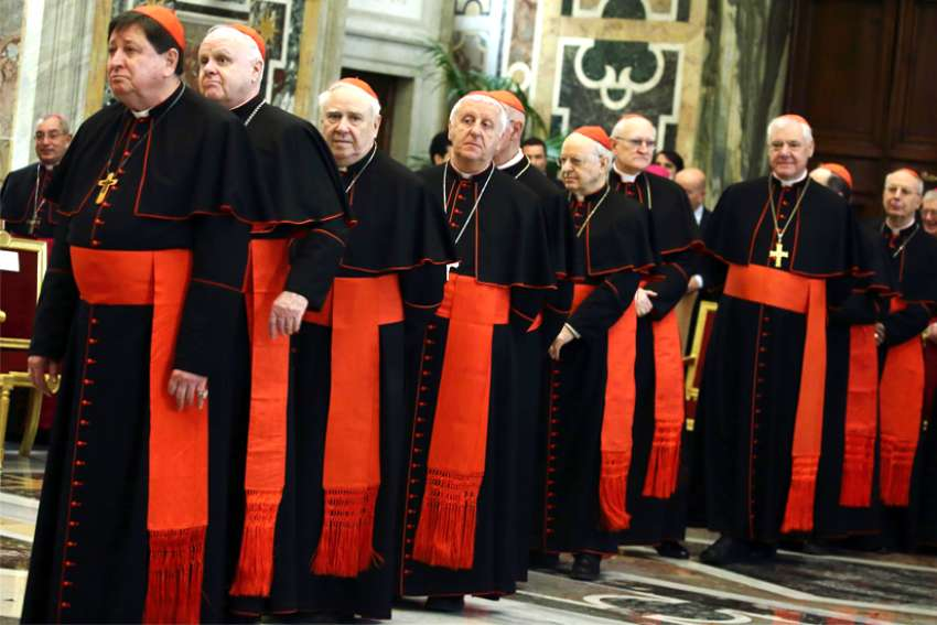 Cardinals wait in line to meet Pope Francis during his annual pre-Christmas meeting with top officials of the Roman Curia at the Vatican in this Dec. 21, 2017, file photo. The pope is planning a major reorganization of the Roman Curia.
